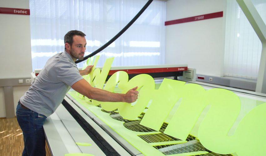 Ein Mitarbeiter entnimmt ein Acryl-Schild aus dem Laser Cutter. Foto: Trotec